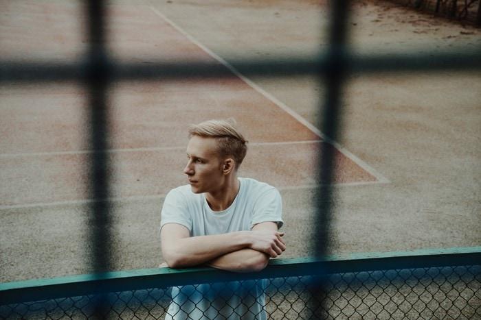 Junger Mann steht auf einem Tennisplatz und macht Pause.
