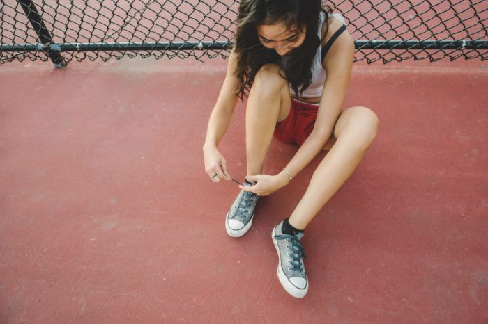 Young woman tying shoelace on basketball court