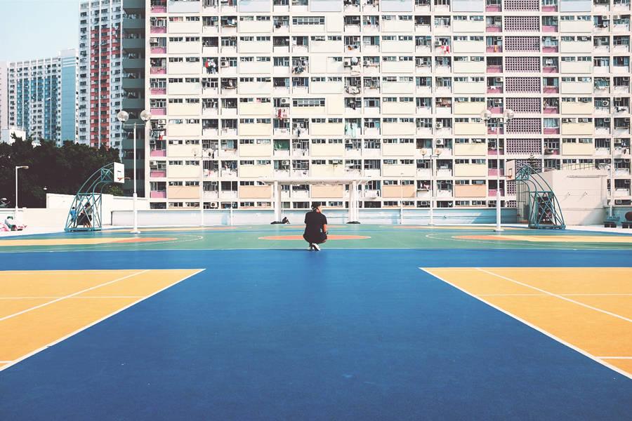 Sportler hockt auf Basketballplatz in einer Großstadt.