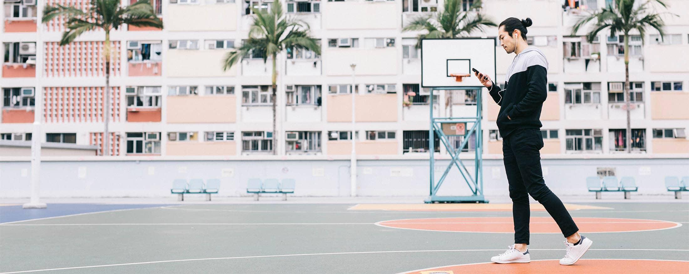 Junger asiatischer Basketballspieler, der auf einem Basketballplatz steht und Musik hört.