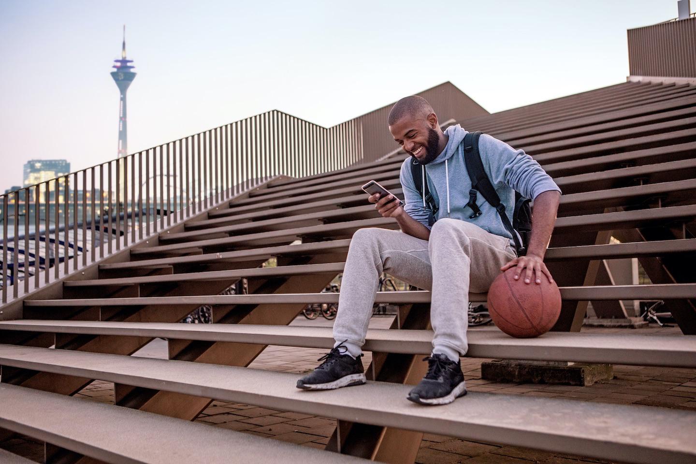 Junger Mann mit Basketball und Smartphone auf einer Treppe