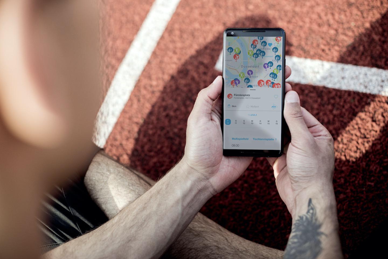 Nahaufnahme eines sitzenden Sportlers mit Smartphone