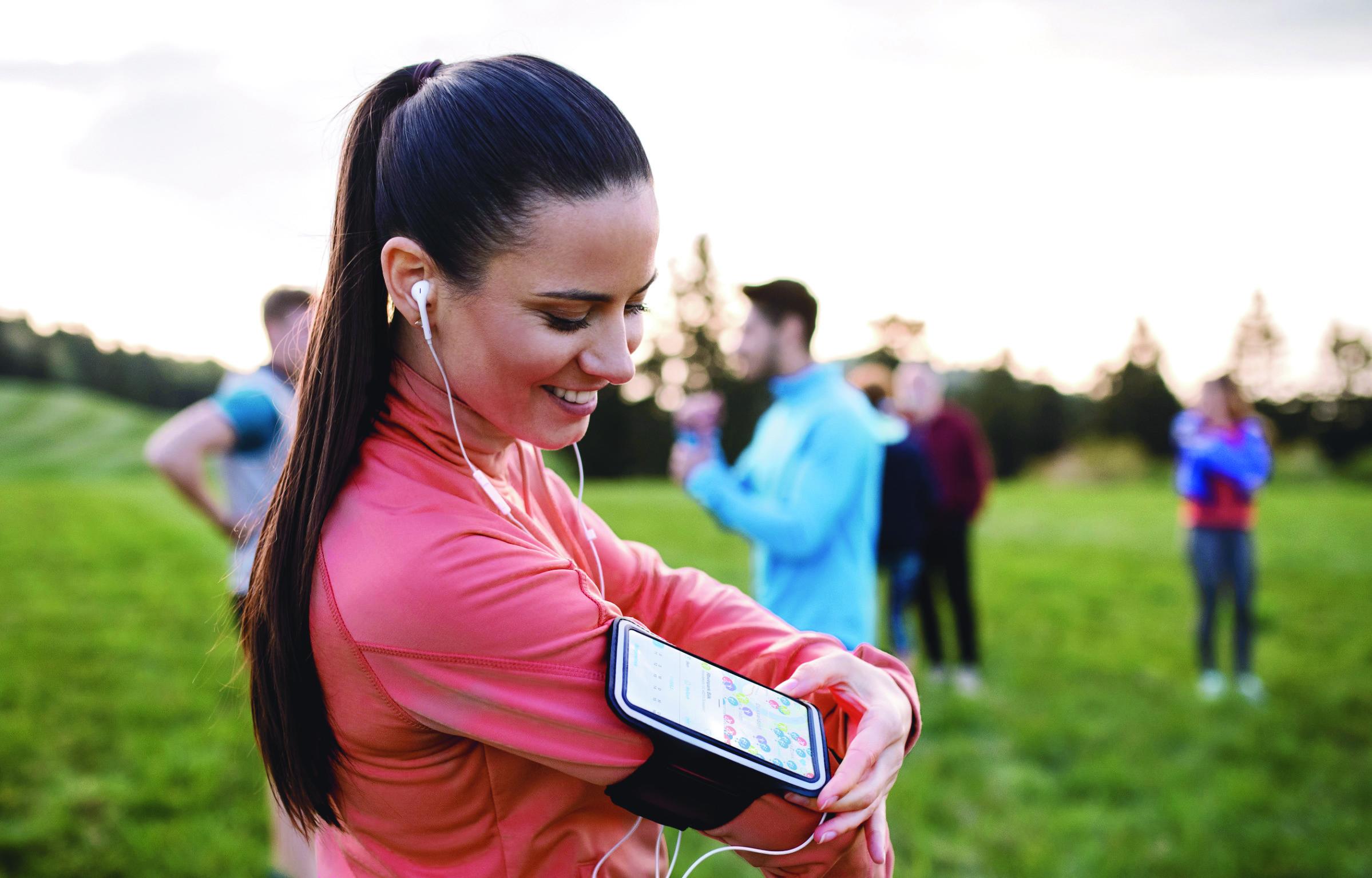 Junge Frau mit Sportgruppe nutzt Smartphone